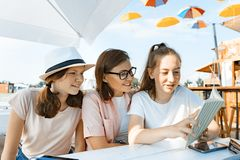 Mamma en dochters de tieners hebben pret, sprekend, kijken en lezen grappig boek Mededeling van de ouder en de kinderen van adole royalty-vrije stock fotografie