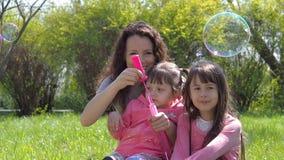 Mamma en dochterslagbellen Familie in het park De kinderen met mamma spelen met bellen Gelukkige familie in aard stock footage