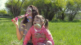 Mamma en dochterslagzeepbels Familie in openlucht Gelukkige familie in park het spelen met bellen stock videobeelden