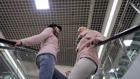 Mamma en dochterstijging op de roltrap stock footage