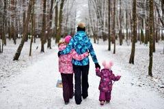 Mamma en haar dochters voor een gang in het hout op de sneeuwwinter stock foto's