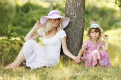 Mamma en haar weinig dochter die in hoeden dichtbij een boom zitten Royalty-vrije Stock Afbeelding