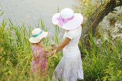 Mamma en haar weinig dochter die in hoeden dichtbij een boom zitten Stock Afbeeldingen