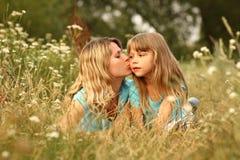 Mamma en haar weinig dochter op het gras Stock Afbeeldingen
