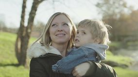 Mamma en haar zoon het kussen Mooi dicht UPS Jonge moeder met haar weinig zoon die en in het park ontspannen spelen Allebei zijn stock footage