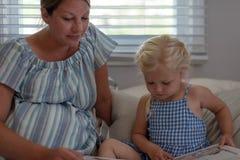 Mamma en jonge dochter die een boek thuis lezen toghethr Stock Afbeelding