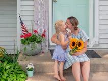 Mamma en jonge dochterzitting op de voorstappen thuis stock foto's