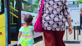 Mamma en kind bij een bushalte, die op de bus wachten stock video
