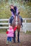 Mamma en kind op het paard Stock Afbeeldingen