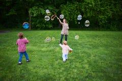 Mamma en kinderen die zeepbels op het groene gazon in het park spelen royalty-vrije stock fotografie