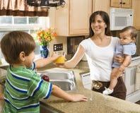 Mamma en kinderen in keuken. stock foto
