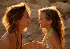 Mamma en meisje op zonsondergang Stock Foto's