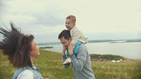 Mamma en papa spelen met het kind op het gebied, het springen die, Papa de baby in zijn wapens houden, bewolking stock footage