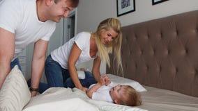 Mamma en vader die haar kind kietelen mensen, familie, pret en ochtendconcept - gelukkig kind met ouders die in bed kietelen bij stock videobeelden