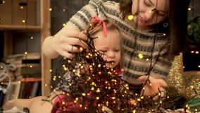 Mamma en weinig dochter die met slingers spelen De jonge moeder en haar dochter treffen voorbereidingen om het huis voor te verfr royalty-vrije stock foto's