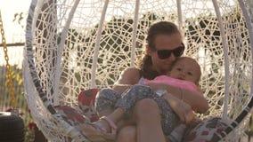 Mamma en weinig dochter die pret op de schommeling hebben stock videobeelden