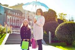 Mamma en weinig dochter het gelukkige winkelen Stel - de achtergrond is vierkante Europese stad, die het winkelen zakken houden royalty-vrije stock foto's