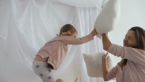 Mamma en weinig dochterstrijd met hoofdkussens stock videobeelden