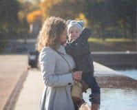 Mamma en weinig zoon onder dalende waterdalingen Royalty-vrije Stock Foto's