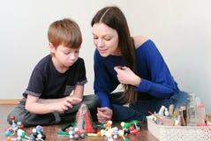 Mamma en zoon die chemische reactie met gasemissie bekijken Ervaring met plasticinevulkaan thuis stock afbeelding
