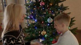Mamma en zoon die en onder de gelukkige familie van de Kerstmisboom slaan glimlachen stock footage