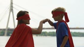 Mamma en zoon in het ponsenvuisten van superherokostuums, concept groepswerk, succes stock video