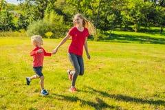 Mamma en zoon op het groene gras in werking dat wordt gesteld dat Gelukkige familie in het park stock afbeelding
