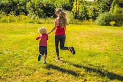 Mamma en zoon op het groene gras in werking dat wordt gesteld dat Gelukkige familie in het park royalty-vrije stock afbeeldingen