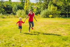 Mamma en zoon op het groene gras in werking dat wordt gesteld dat Gelukkige familie in het park stock foto's