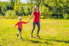 Mamma en zoon op het groene gras in werking dat wordt gesteld dat Gelukkige familie in het park royalty-vrije stock foto's