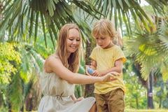 Mamma en zoons de nevel van de gebruiksmug Bespuitend insektenwerend middel op huid royalty-vrije stock afbeelding