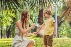 Mamma en zoons de nevel van de gebruiksmug Bespuitend insektenwerend middel op huid openlucht royalty-vrije stock foto