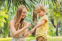 Mamma en zoons de nevel van de gebruiksmug Bespuitend insektenwerend middel op huid openlucht royalty-vrije stock afbeelding