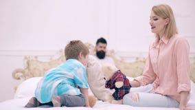 Mamma en zoons het spelen met zacht speelgoed in bed en vader die een boek op de achtergrond lezen Het concept een gelukkige fami stock videobeelden