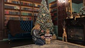 Mamma en zoons open Kerstmisgiften dichtbij de boom stock video