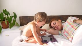 Mamma en zoonshorlogetablet in slaapkamer stock footage