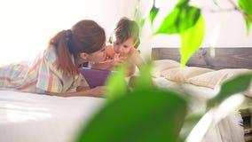 Mamma en zoonshorlogetablet in slaapkamer stock videobeelden