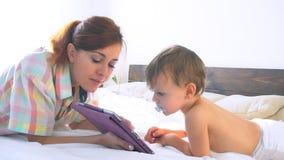 Mamma en zoonshorlogetablet in slaapkamer stock video