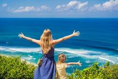 Mamma en zoonsreizigers op een klip boven het strand Leeg paradijs royalty-vrije stock foto