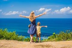 Mamma en zoonsreizigers op een klip boven het strand Leeg paradijs stock foto
