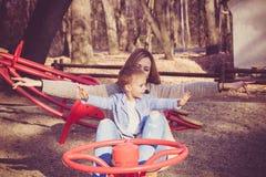 Mamma en zoonsspel in park Stock Foto