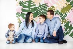 Mamma, farsa och två unga barn som sitter på golvet Concepen fotografering för bildbyråer