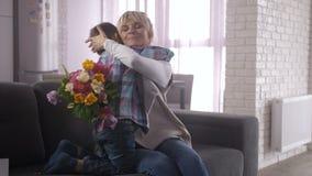 Mamma felice che abbraccia figlio sveglio sul sofà alla festa della mamma