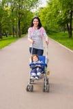 Mamma felice che spinge carrozzina con il bambino in parco Fotografia Stock
