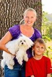Mamma felice con il suo bambino e un cane di animale domestico Fotografia Stock