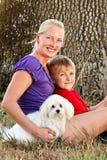 Mamma felice con il suo bambino e un cane di animale domestico Fotografie Stock Libere da Diritti