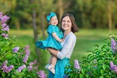 Mamma felice della madre con la figlia che gode del tempo su un posto impressionante fra il cespuglio lilla della siringa Giovani Fotografie Stock Libere da Diritti