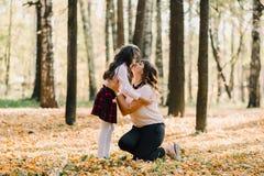 Mamma felice e figlia nel parco che baciano nella caduta Fotografia Stock