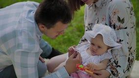 Mamma felice e papà della famiglia che giocano con il bambino sul copriletto archivi video