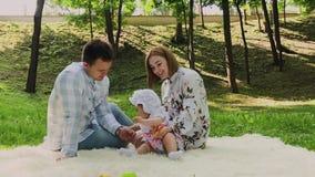 Mamma felice e papà della famiglia che giocano con il bambino sul copriletto video d archivio